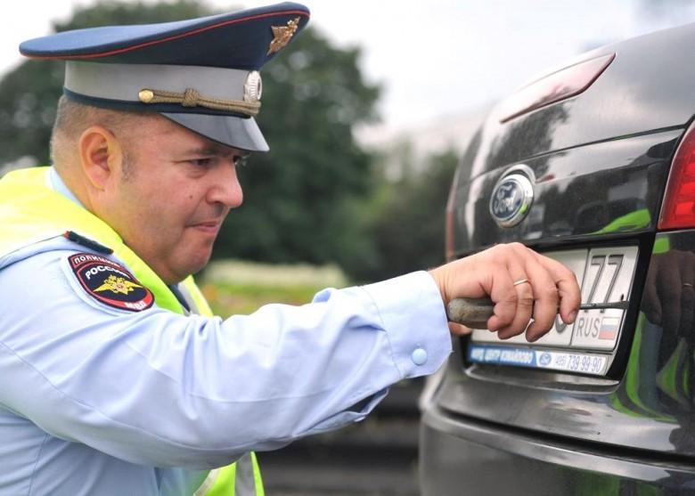 Инспектор ГИБДД снимает номера ТС