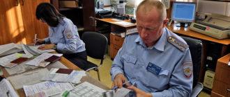 Инспектор ГИБДД проверяет документы на авто при регистрации транспортного средства